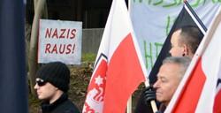 Neonazis vor Protestschildern der Bevölkerung